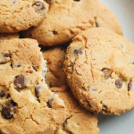 Chocolate chip cookies on a plate with the words, 'More than two dozen delicious recipes with chocolate chips'.