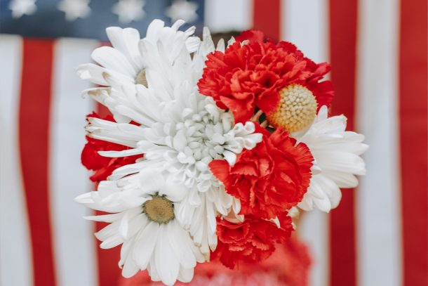 Red and white flowers in front of an American flag.