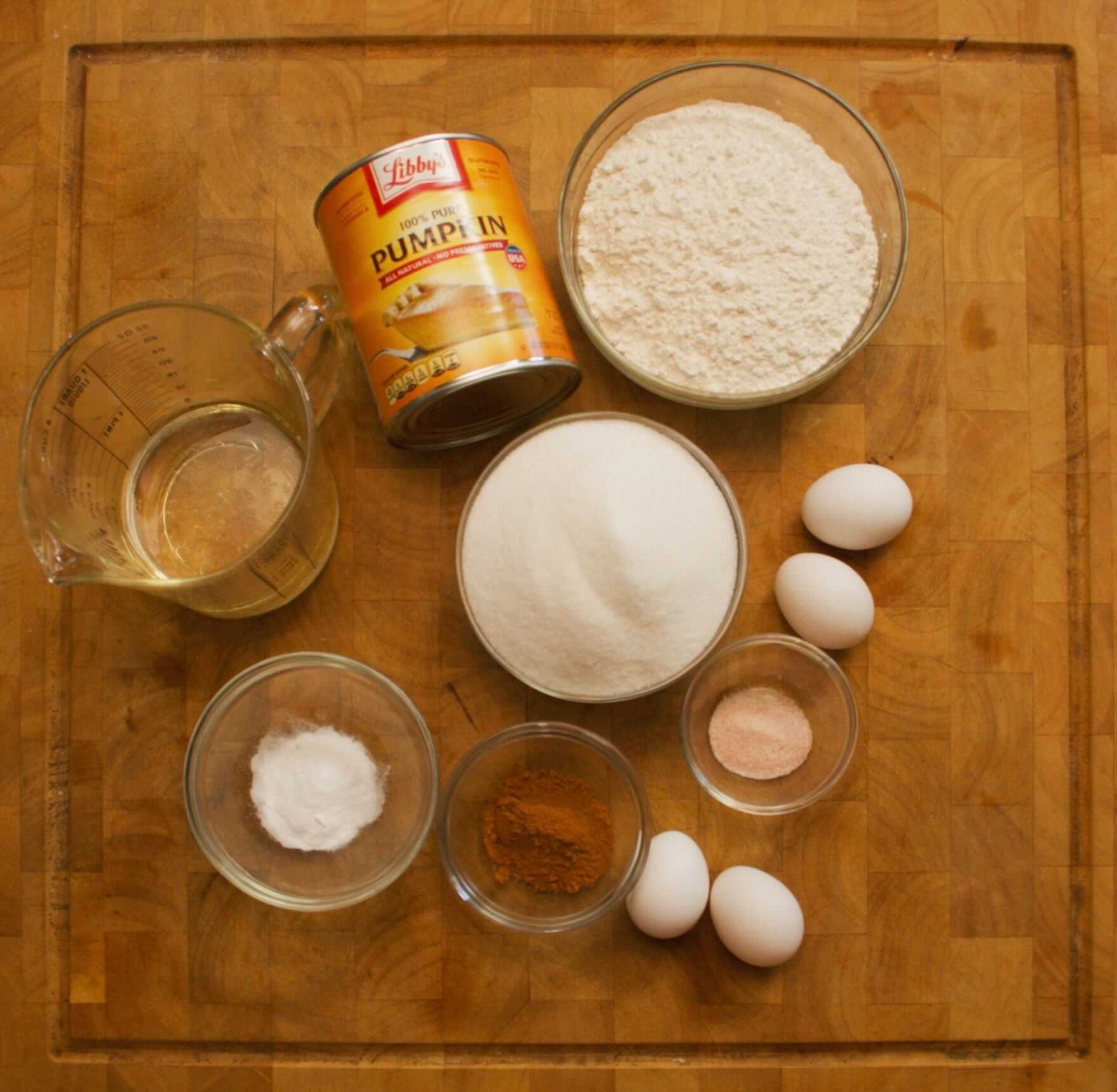 Ingredients for pumpkin bread recipe in a circle on a wooden cutting board.