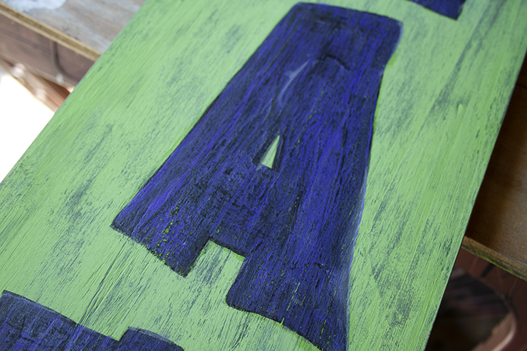 Close up of the letter A on a green sign. The letter has been sanded to give it a more weathered look.