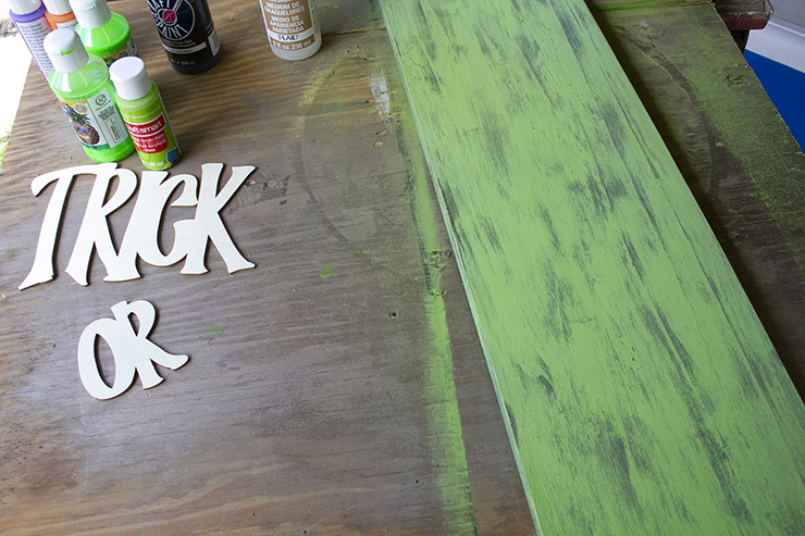 Board painted bright green, and then sanded, to reveal the black paint below.