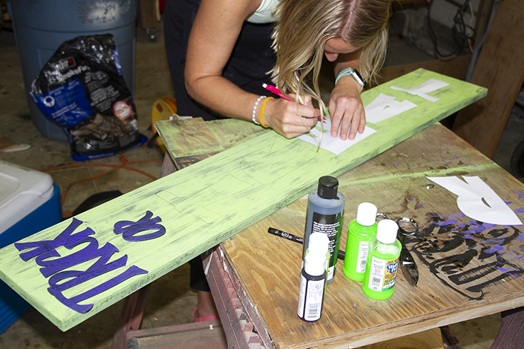 Blond woman painting letters on a large green, wooden sign.