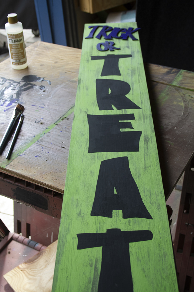 Green sign with letters painted on it.