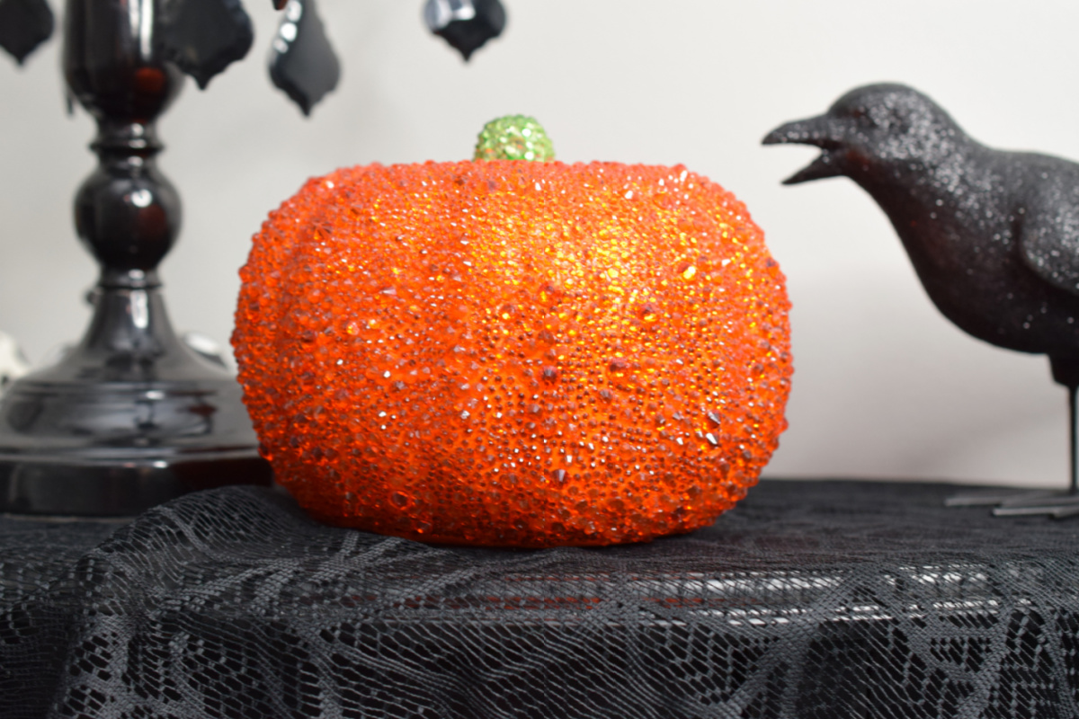 Sparkly orange pumpkin sitting on a black, lace tablecloth with a black bird in the background.