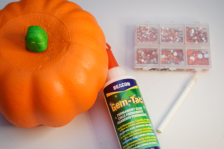 Supplies for blinged pumpkin - styrofoam pumpkin, rhinestones, gem-tac, and pencil.