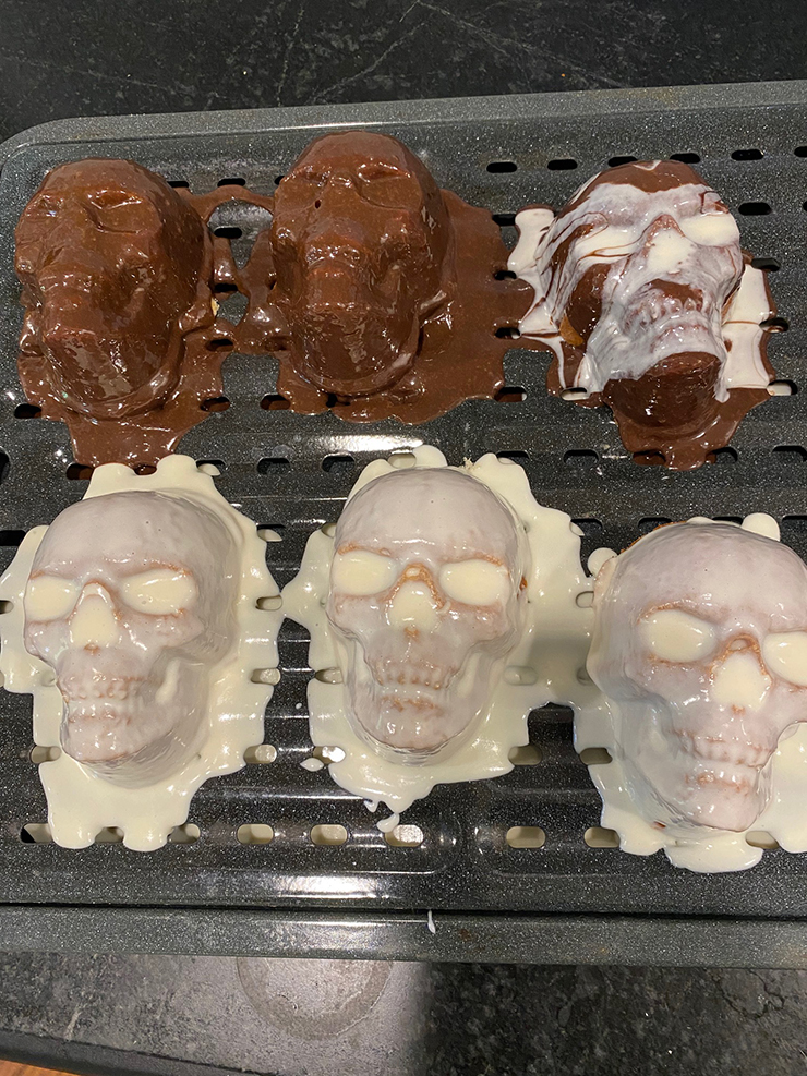 Skull cakes on a cooling rack with frosting poured over them, drying.