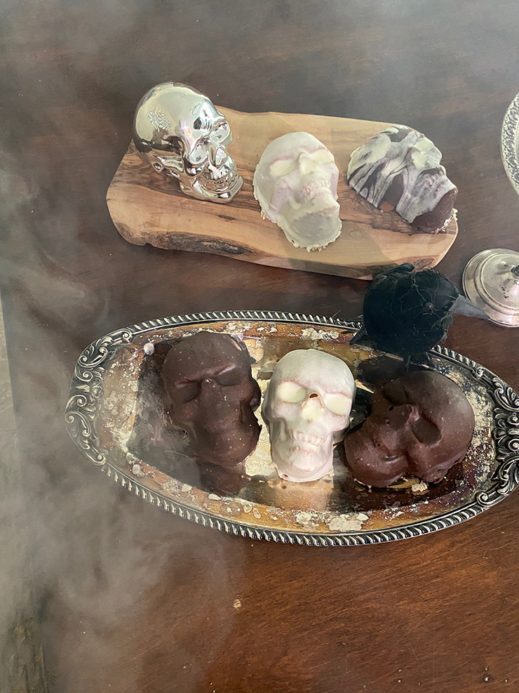 Mini cakes in the shape of skulls with brown and white frosting, sitting on a table with smoke all around them.